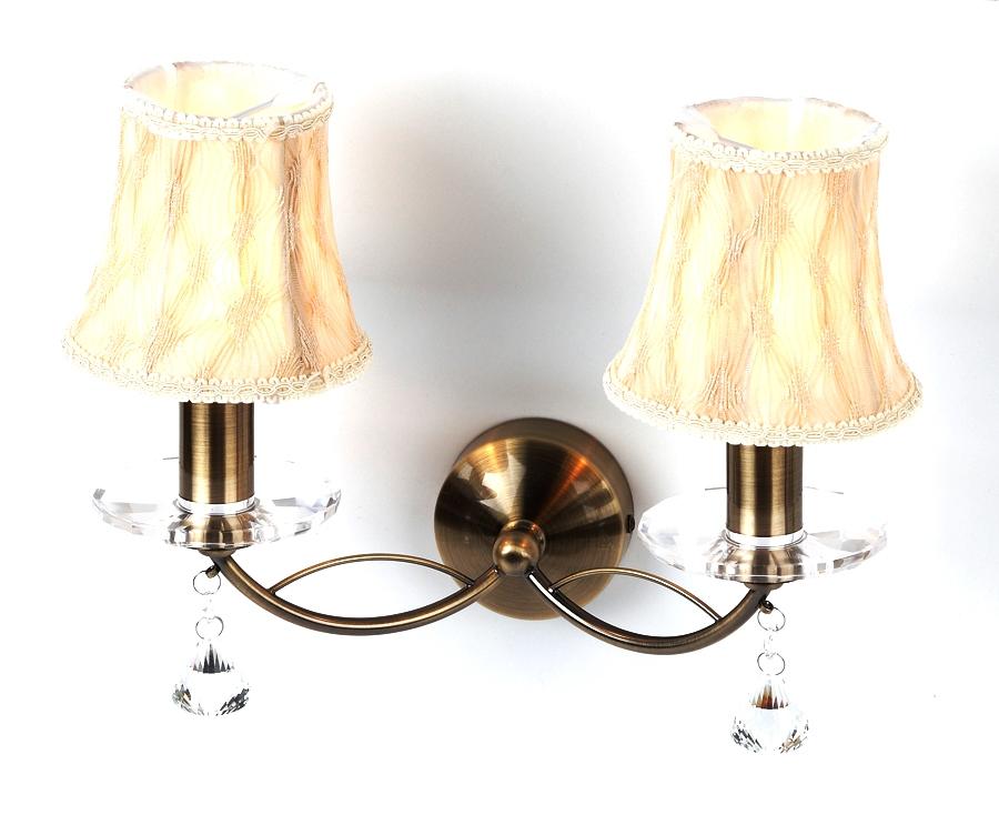 Бра RivoliНастенные светильники и бра<br>Тип: бра,<br>Назначение светильника: для комнаты,<br>Стиль светильника: классика,<br>Материал светильника: металл, ткань,<br>Тип лампы: накаливания,<br>Количество ламп: 2,<br>Мощность: 60,<br>Патрон: Е14,<br>Цвет арматуры: латунь,<br>Длина (мм): 240,<br>Ширина: 345,<br>Высота: 300<br>